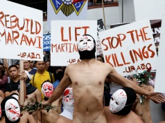 Naked mebers of the APO fraternity wearing masks attend a protest in Quezon city