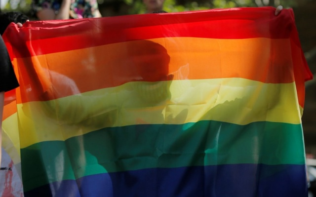 A supporter of same-sex marriage in Australia is pictured through a rainbow flag during protest near a counter-demonstration against same-sex marriage at a park in Sydney