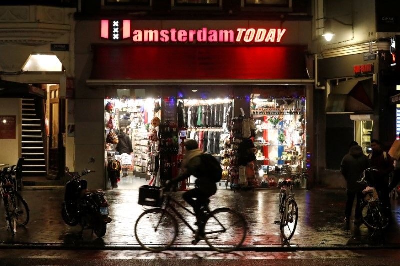 A cyclist rides past a touristic shop in Amsterdam
