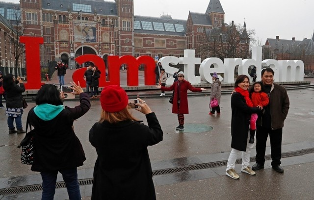 Tourists pose for photos outside the Rijksmuseum in central Amsterdam