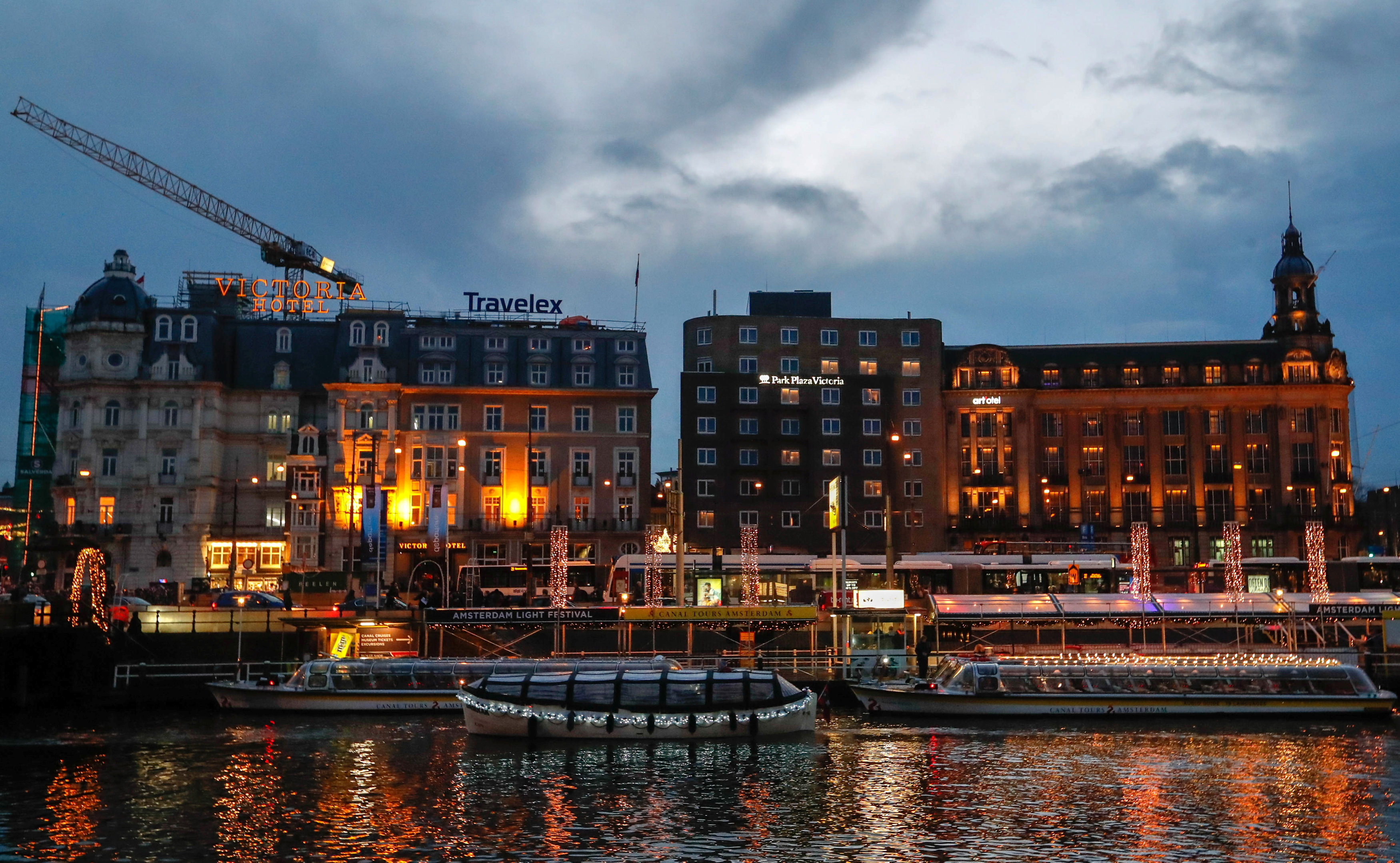 Touristic boats are illuminated while cruising on a canal in central Amsterdam