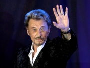 "French singer Johnny Hallyday waves to fans attending a ceremony to promote his new album ""Jamais seul"" (Never alone) at the Virgin Megastore in Paris"