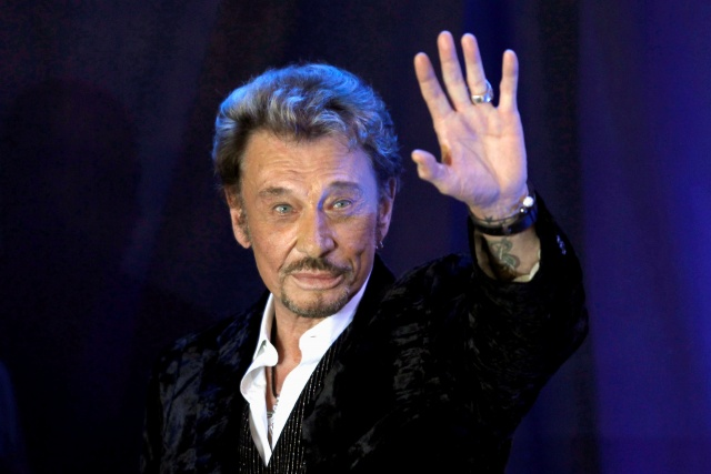 French singer Johnny Hallyday waves to fans attending a ceremony to promote his new album