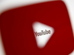 A 3D-printed YouTube icon is seen in front of a displayed YouTube logo in this illustration