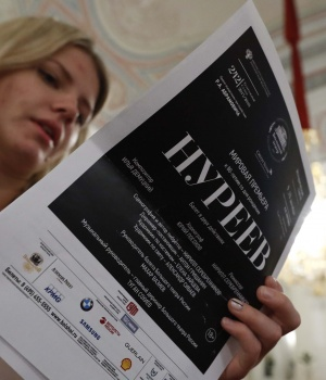 "A journalist holds leaflets of the ""Nureyev"" ballet by director Kirill Serebrennikov, about the late Soviet ballet dancer Rudolf Nureyev, during a news conference ahead of the ballets's premiere at the Bolshoi Theatre in Moscow"