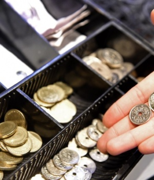 A waitress poses with some coins in front of a cash-box of Danish crowns in a pub in Copenhagen