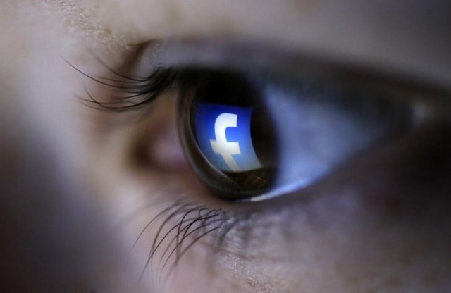 A picture illustration shows a Facebook logo reflected in a person's eye, in Zenica