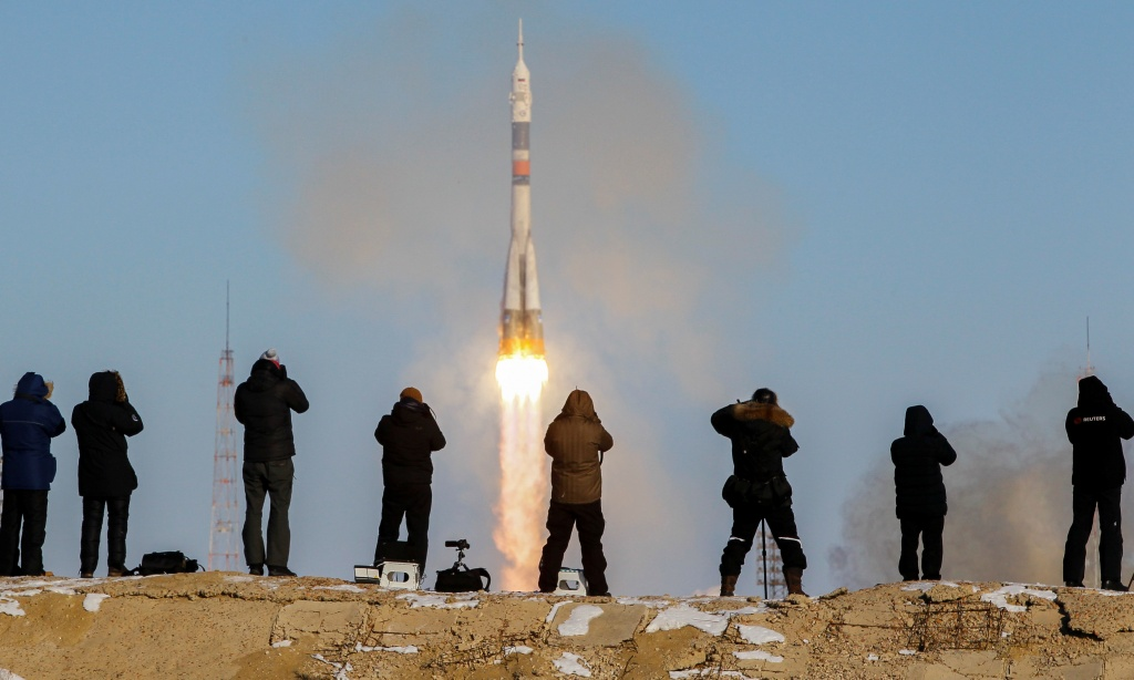 Photographers take pictures as the Soyuz MS-07 spacecraft carrying the next International Space Station (ISS) crew blasts off from the launchpad at the Baikonur Cosmodrome
