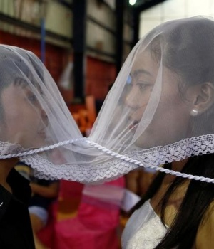 A couple wear a veil during a same sex wedding ceremony officiated by Reverend CJ Agbayani of the Christian Church Inc in Quezon city, Metro Manila