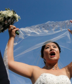 A bride reacts during a mass wedding ceremony for fifty Chinese couples in Colombo