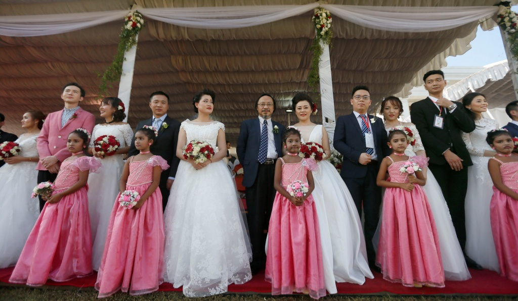 Couples pose for photographs during a mass wedding ceremony for fifty Chinese pairs in Colombo
