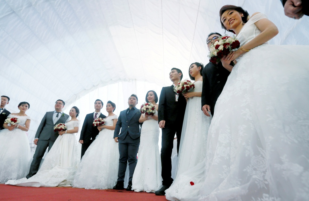 Chinese wedding couples take part during a mass wedding ceremony for fifty Chinese couples in Colombo