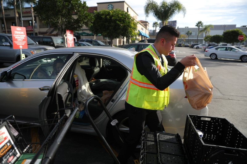 A Ralph's grocery store employee serves a customer who has used Kroger's ClickList online ordering and curbside pickup service in Los Angeles