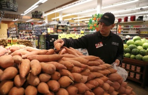 A Ralph's grocery store employee loads a cart for a customer who has used Kroger's ClickList online ordering and curbside pickup service in Los Angeles