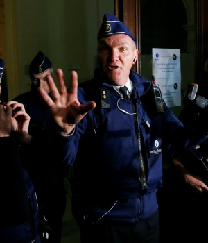 Belgian police officer gestures outside the trial of Paris attacks suspect Abdeslam in Brussels