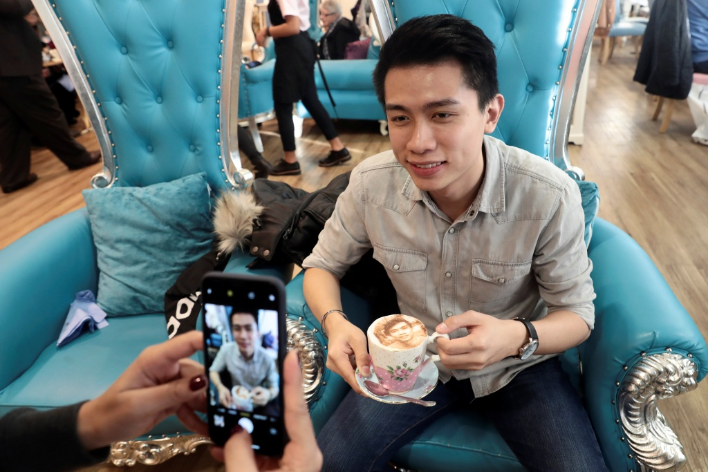 A customer poses for a photo with his 'Selfieccino' coffee at the Tea Terrace in London