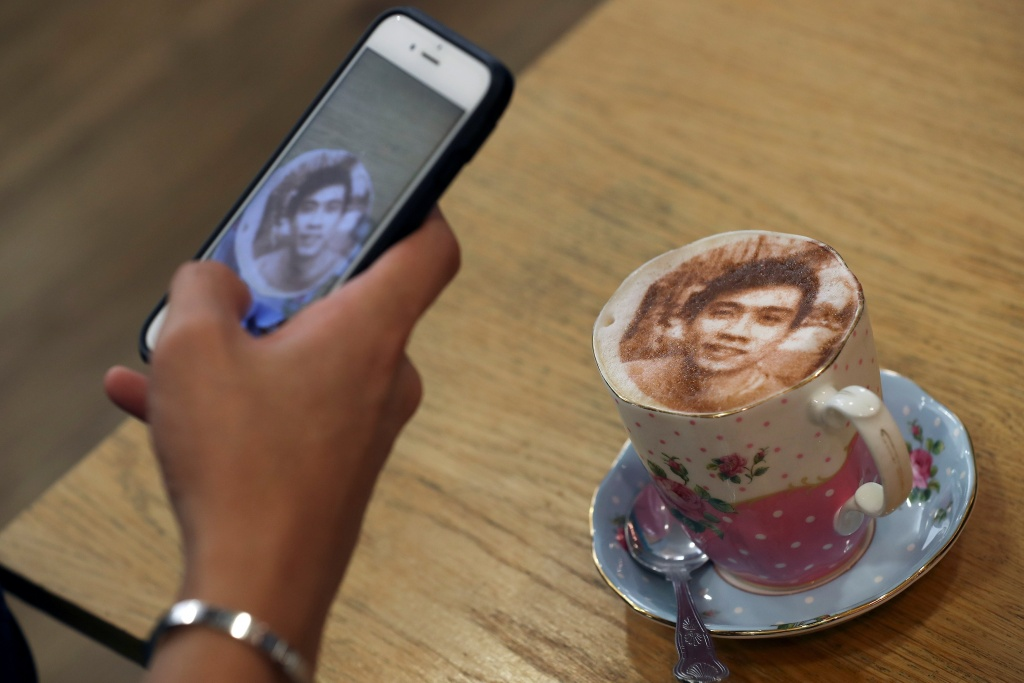 A customer takes a photograph of their 'Selfieccino' coffee at the Tea Terrace in London