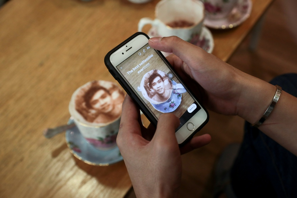 A customer loads a photograph of his 'Selfieccino' coffee' on social media at the Tea Terrace in London