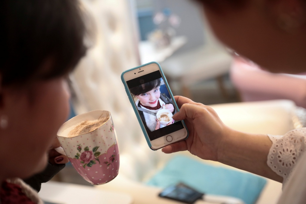 A customer looks at a photograph of herself drinking a 'Selfieccino' coffee at the Tea Terrace in London