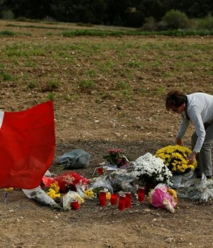 A woman places flowers at the scene of the assassination of investigative journalist Daphne Caruana Galizia, killed in a car bomb attack a week ago, alongside the road leading from her home in Bidnija