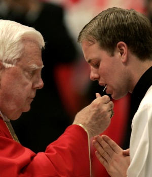U.S. Cardinal Bernard Law (L) gives the host to a young priest during a Mass in the Vatican's St. Peter's Basilica