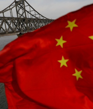A Chinese flag is seen in front of the Friendship bridge over the Yalu River connecting the North Korean town of Sinuiju and Dandong in China