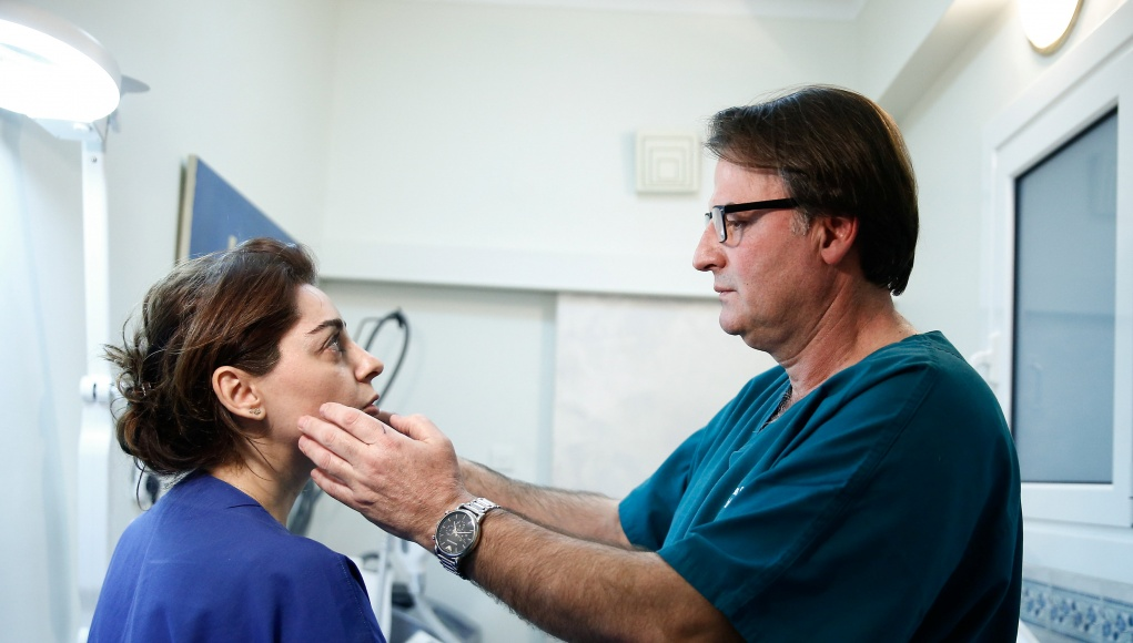 Stathakis examines a customer's face following a Botox injection at his office in Athens