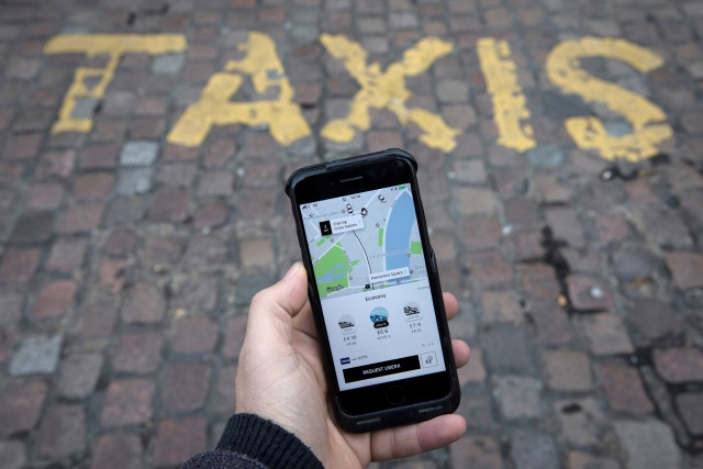 A photo illustration shows the Uber app on a mobile telephone, as it is held up for a posed photograph, in London