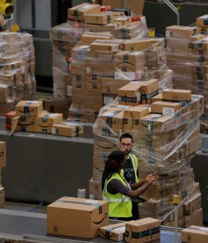 Workers walk past boxes to be shipped inside of an Amazon fulfillment center in Robbinsville, New Jersey