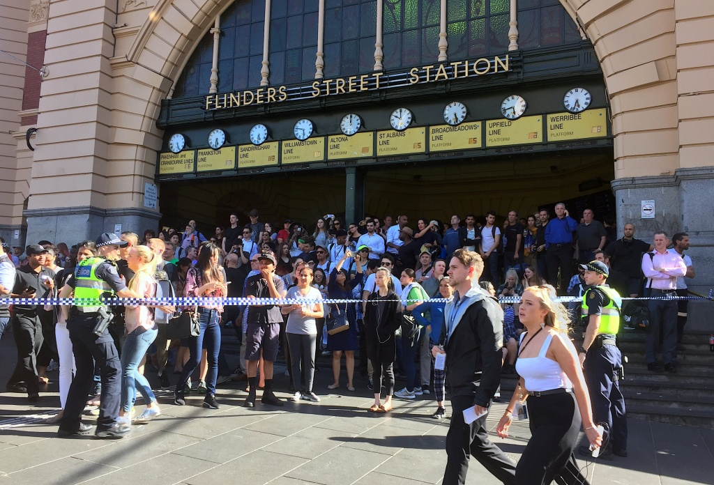 Members of the public stand behind police tape after Australian police said on Thursday they have arrested the driver of a vehicle that ploughed into pedestrians at a crowded intersection near the Flinders Street train station in central Melbourne