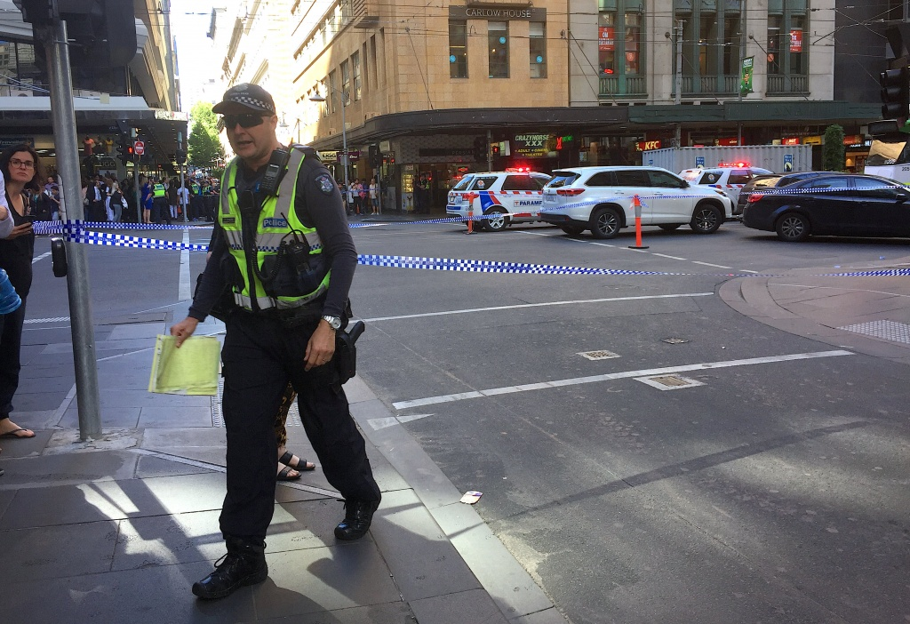Police officers secure the area as members of the public stand behind police tape after the arrest of the driver of a vehicle that ploughed into pedestrians at a crowded intersection near the Flinders Street train station in central Melbourne
