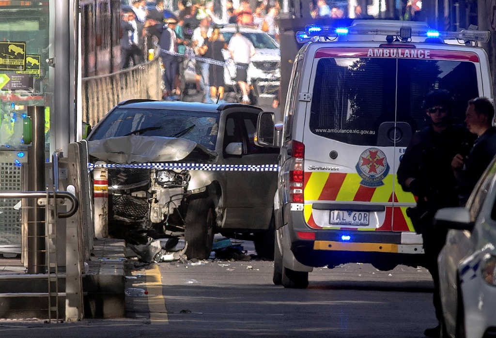 Australian police stand near a crashed vehicle after they arrested the driver of a vehicle that had ploughed into pedestrians at a crowded intersection near the Flinders Street train station in central Melbourne