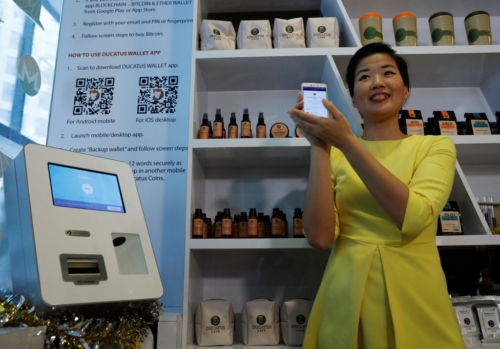 Ducatus cafe operations manager Frances Sy introduces a Bitcoin ATM at the opening of their cashless cafe that accepts cryptocurrencies such as Bitcoin in Singapore