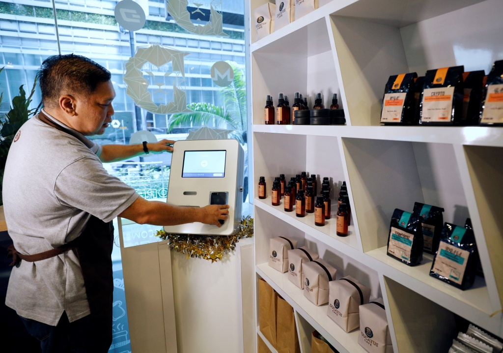 Ducatus franchise manager Philip Lim shows how a deposit is made at a Bitcoin ATM at the opening of their first cashless cafe that accepts cryptocurrencies such as Bitcoin in Singapore
