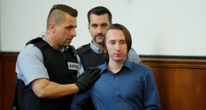 A man suspected of detonating three bombs targeting the Borussia Dortmund soccer team bus in April, Sergej W, arrives to stand trial at a German state court in Dortmund