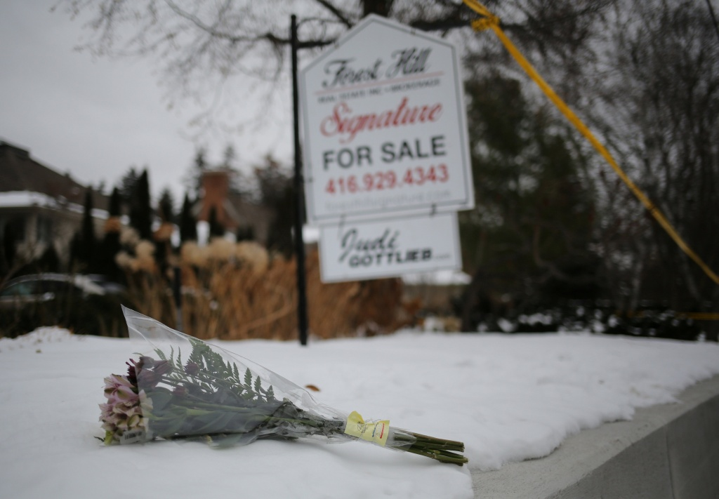 Flowers from mourners are seen outside the home of billionaire founder of Canadian pharmaceutical firm Apotex in Toronto
