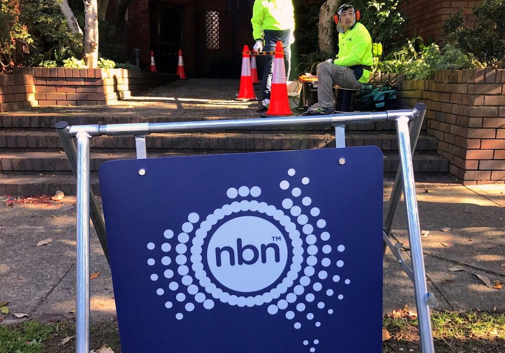 Workers install cables for the Australian National Broadband Network at an apartment block in Sydney