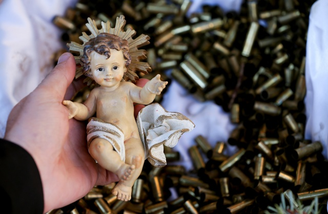 A monk holds a statue of the baby Jesus taken from a bed of bullet shells from a Nativity scene outside the Basilica of St Francis in Assisi