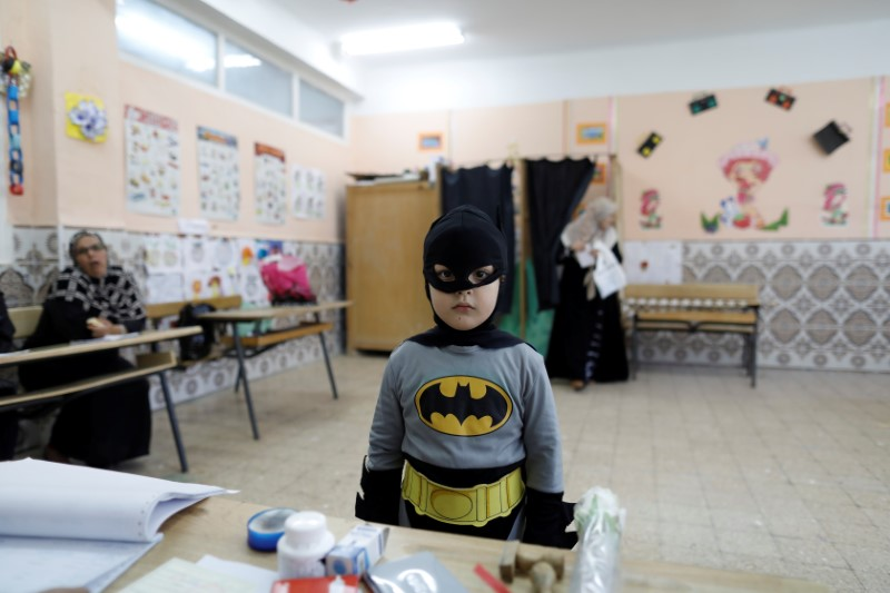 A boy in a Batman costume stands at a polling station during the parliamentary election in Algiers