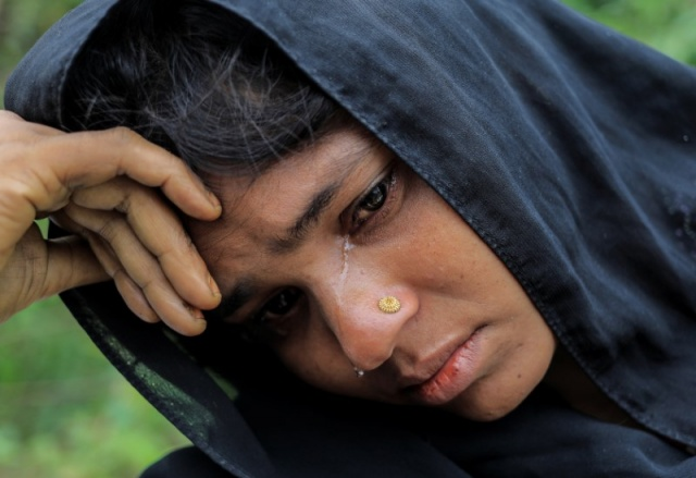 A Rohingya refugee woman who crossed the border from Myanmar this week cries while waiting to get a shelter in Kotupalang refugee camp near Cox's Bazar