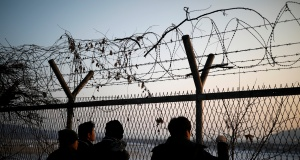 People look toward the north through a barbed-wire fence near the militarized zone separating the two Koreas, in Paju