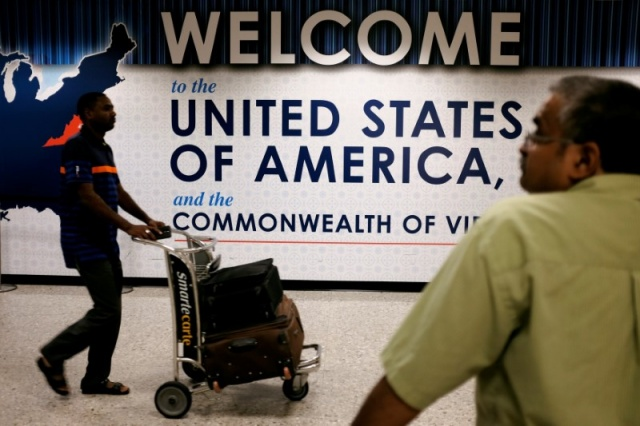 An international passenger arrives at Dulles International Airport as a man waits for loved ones to arrive in Dulles, Virginia