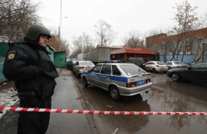 """A policeman stands guard after a gunman opened a fire in the pastry-making factory """"Menshevik"""" in Moscow"""