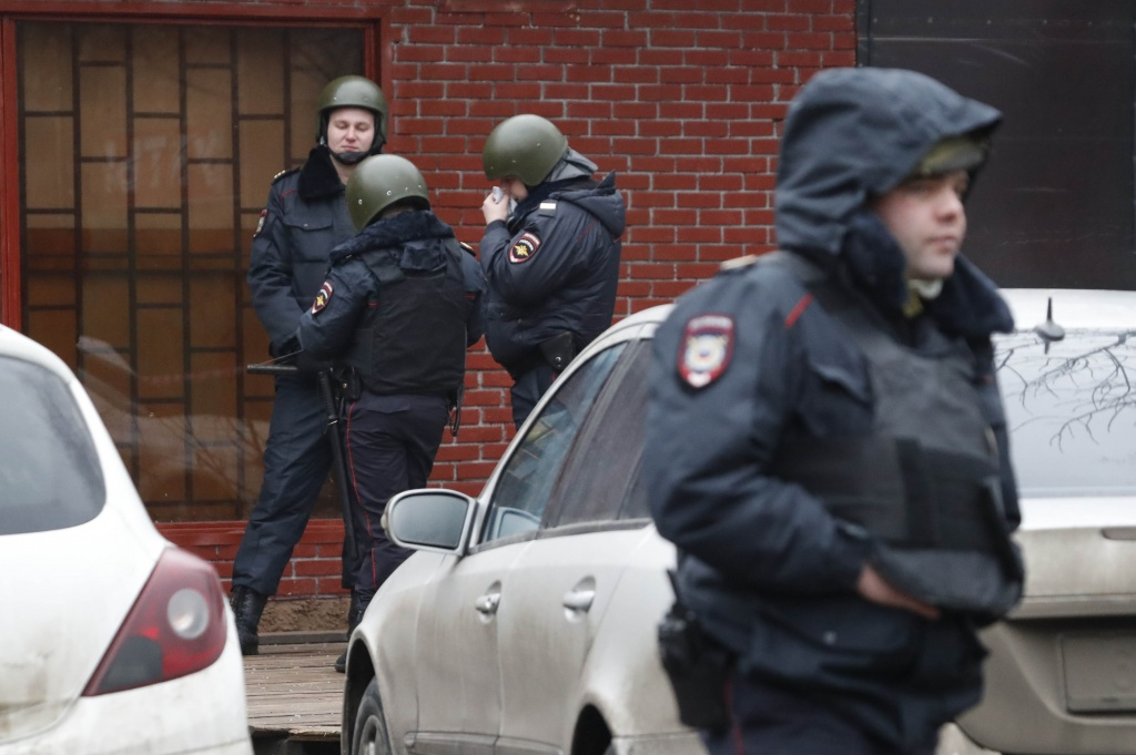 "Policemen stand guard after a gunman opened a fire in the pastry-making factory ""Menshevik"" in Moscow"
