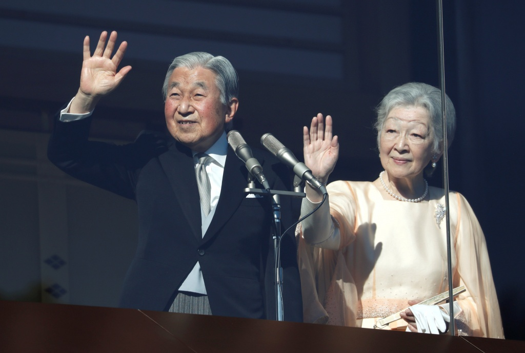 Japan's Emperor Akihito, flanked by Empress Michiko, waves to well-wishers who gathered at the Imperial Palace to mark his 84th birthday in Tokyo
