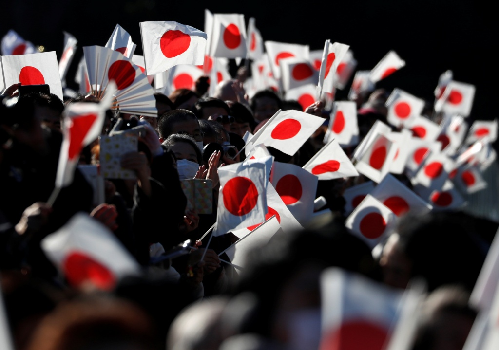Well-wishers wave Japanese national flags as Japan's Emperor Akihito appears on a balcony of the Imperial Palace to celebrate his 84th birthday in Tokyo