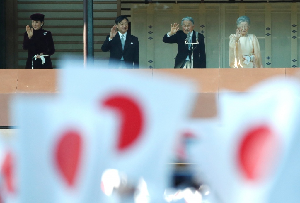 Japan's Emperor Akihito, flanked by Empress Michiko, Crown Prince Naruhito and Crown Princess Masako, is seen through Japanese national flags as he waves to well-wishers who gathered at the Imperial Palace to mark his 84th birthday in Tokyo