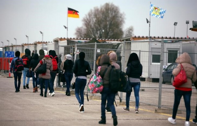 Eritrean migrants walk after arriving by plane from Italy at the first registration camp in Erding