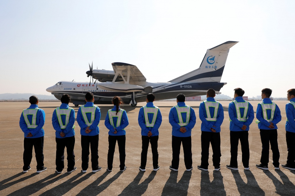 Members of ground staff stand in front of China's domestically developed AG600, the world's largest amphibious aircraft, after it lands on its maiden flight in Zhuhai