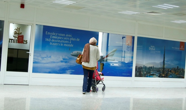 A women are seen in front of the Dubai airline Emirates office, at Tunis-Carthage International Airport in Tunis